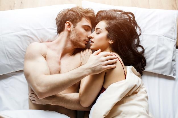 若いセクシーなカップルは、ベッドに親密さを持っています。寝ているポーズで横になっています。抱き合うキス。ベッドで一緒に情熱的なカップル。白色の背景。明け。ビューティフル・ピープル。 Premium写真