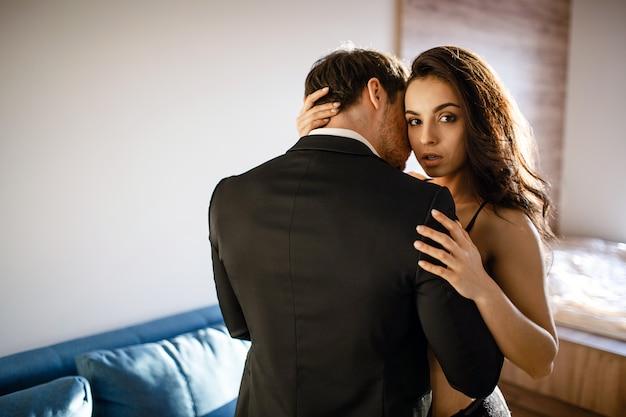 リビングルームで若いセクシーなカップル。黒のランジェリーで美しい魅力的な若い女性は男を受け入れ、カメラに見えます。情熱を持ったビジネスマンタッチモデル。 Premium写真