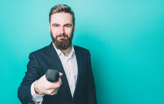 Счастливый человек стоит и смотрит прямо вперед. он держит микрофон для интервью. парень выглядит уверенно. Premium Фотографии