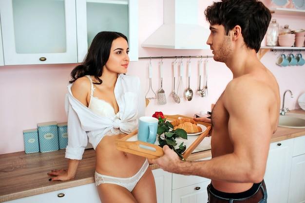 白いシャツでゴージャスな若い女性は男に見えます。彼らは台所にいます。立派な男は、朝食と赤いバラのトレイを保持します。彼らは満足している。 Premium写真
