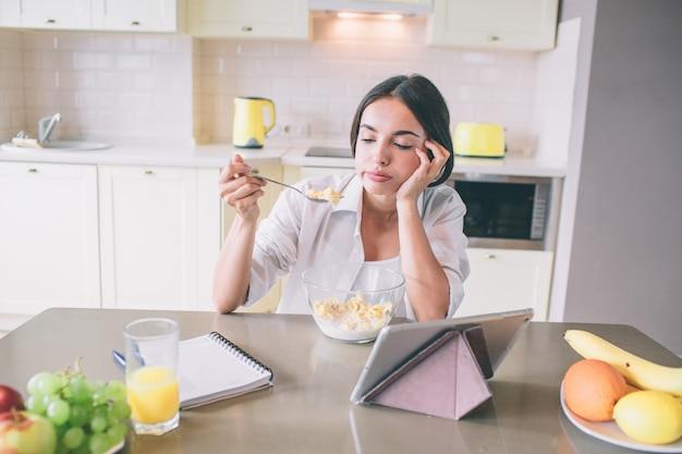 Усталая и скучающая девушка сидит за столом и смотрит на ложку с молоком и кукурузными хлопьями. Premium Фотографии