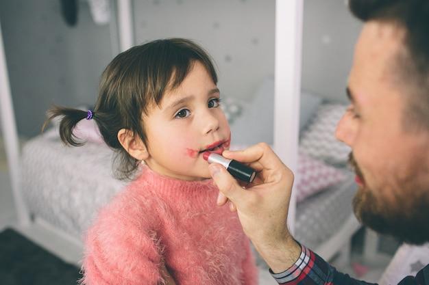 Милая маленькая дочь и ее красивый молодой папа играют вместе в детской комнате. девушка делает ее папа макияж. Premium Фотографии