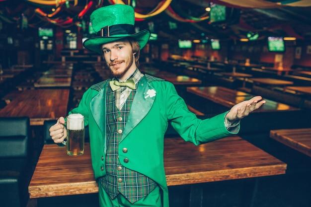 ビールと外観のマグカップを保持している緑のスーツの若い赤毛の男。彼は脇に手を握る。 Premium写真