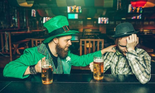 Пьяные молодые люди сидят за барной стойкой в пабе. парень в зеленом костюме трогает своего друга. у молодого человека слева похмелье. у них есть кружки пива. Premium Фотографии