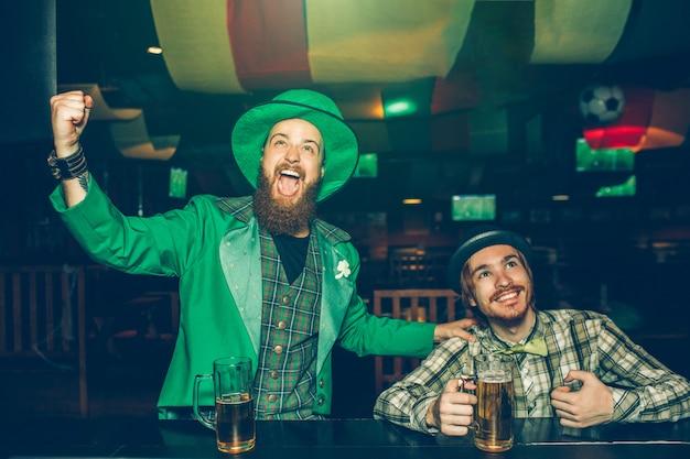 Веселые молодые люди сидят за барной стойкой в пабе и восхищаются. они смотрят вперед. ребята держат кружки пива на барной стойке. молодой человек слева носить зеленый костюм. Premium Фотографии