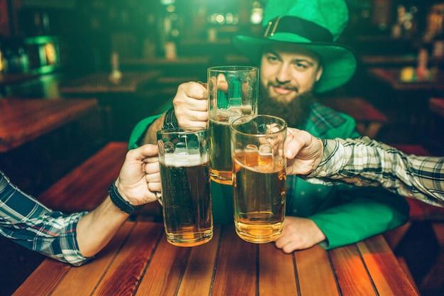Изображение молодого человека в костюме зеленого святого патрика сидеть за столом с друзьями в пабе. они держат кружки пива вместе. Premium Фотографии