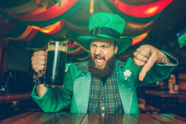 Расстроенный и отвратительный молодой человек в позе зеленого костюма. он сидит за столом в пабе и показывает большой палец вниз. молодой человек держать кружку темного пива. Premium Фотографии