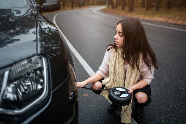 路上で壊れた車のエンジン車の修理を見て混乱している若い女性 Premium写真
