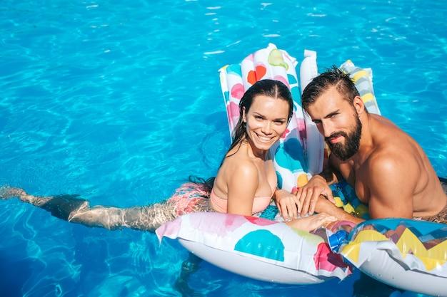素敵で若いカップルがエアマットレスに寄りかかって見えます。彼らはポーズを取る。女の子は笑っています。男のまばたき彼らは幸せそうに見えます。 Premium写真