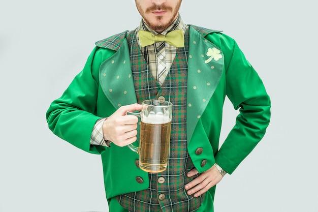 ビールのジョッキを保持している緑のスーツの若い男のビューをカットします。彼はもう一方の手を腰に当てます。男は聖パトリックのスーツを着ます。グレーに分離。 Premium写真