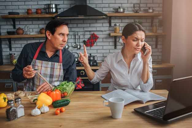 忙しい女性がテーブルに座って電話で話す Premium写真