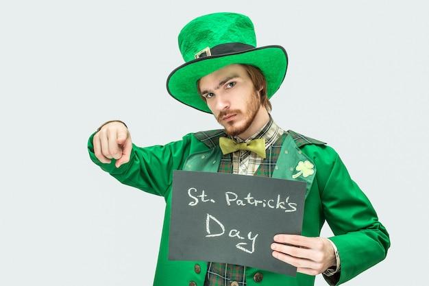 聖パトリックの書き込みで暗いタブレットを保持している緑のスーツの若い男。彼はまっすぐ指さして見ている。グレーに分離。 Premium写真