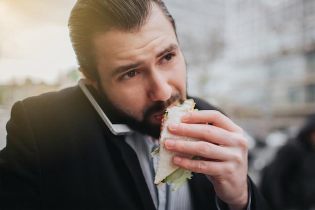 Занятый человек спешит, у него нет времени, он собирается перекусить на ходу. работник ест, пьет кофе, разговаривает по телефону, одновременно. бизнесмен делает несколько задач. Premium Фотографии