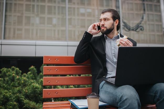 Занятый человек спешит, у него нет времени. работник ест и работает с документами на ноутбуке одновременно. бизнесмен делает несколько задач. многозадачность делового человека. Premium Фотографии