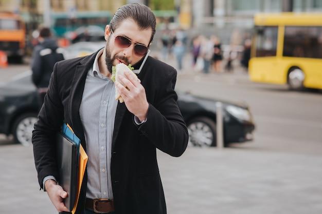 Работник ест, пьет кофе, разговаривает по телефону, одновременно. бизнесмен делает несколько задач. многозадачность делового человека. Premium Фотографии