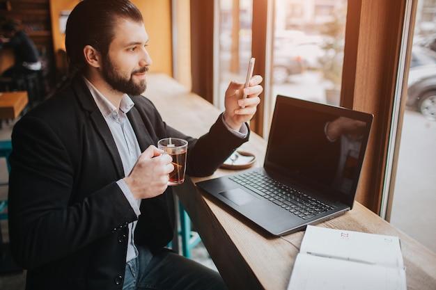 忙しい人は急いでいます、彼には時間がありません、彼は食事をして仕事をするつもりです。労働者が食事をし、コーヒーを飲み、電話で話していると同時に。複数のタスクを行うビジネスマン。 Premium写真