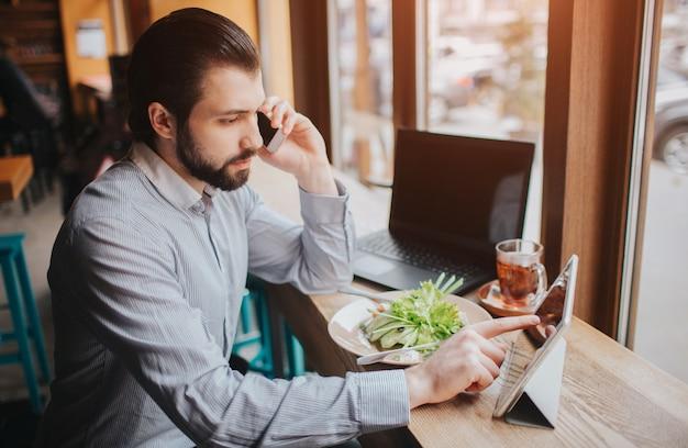 Занятый человек спешит, у него нет времени, он собирается есть и работать. работник ест, пьет кофе, разговаривает по телефону, одновременно. бизнесмен делает несколько задач. Premium Фотографии