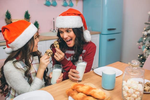 興奮して幸せな若い女性と少女はお互いを見て、クッキーを手に保持します。手には牛乳が入っています。人々は帽子をかぶっています。彼らは台所に座っています。 Premium写真