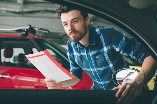 完璧なライン。ディーラーで車を調べ、彼の選択をする若い黒髪のひげを生やした男。車で若い男の水平方向の肖像画。彼はそれを買うべきかと考えている。 Premium写真
