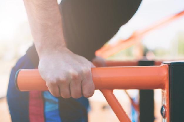 平行棒のディップを行う黒いトレーニング服で筋肉の男 Premium写真