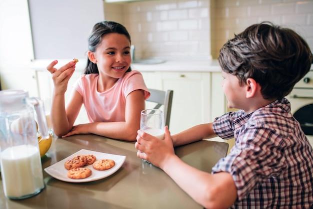 子供たちはテーブルに座っています。彼女はクッキーを食べています。少年はミルクのカップを保持しています。彼らはお互いを見て笑っています。子供たちは一人です。 Premium写真