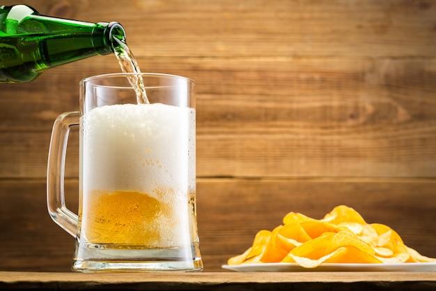 Заполнение стакан с пивом на деревянной стене. Premium Фотографии