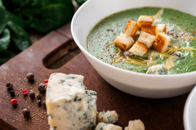 ほうれん草とブロッコリーのグリーンクリームスープ。パルメザンチーズとブルーチーズとクルトンを加えました。木製の表面。 Premium写真