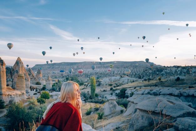 たくさんの風船が愛の谷の上を飛ぶ飛行を見ている夜明けの民族衣装の女の子 Premium写真