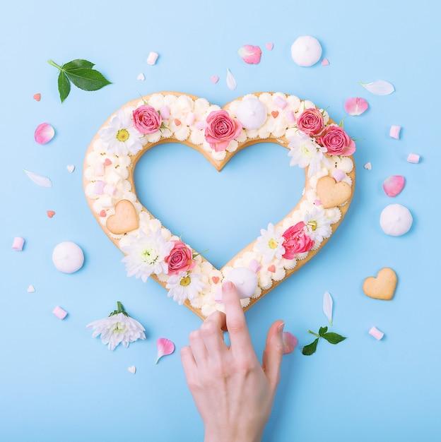 バレンタインのハート型の装飾として花とケーキ。 Premium写真