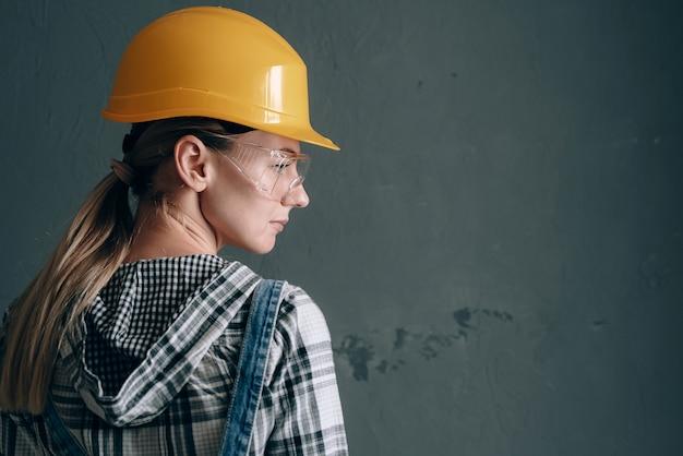 建設用ヘルメット、ミトン、ゴーグル、オーバーオールを着た意欲的な女性が自宅で修理と建設作業に従事しています。強くて自立した女性の概念 Premium写真