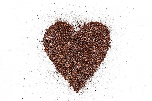 ローストコーヒー豆と白い表面に挽いたコーヒーで作られた心 Premium写真
