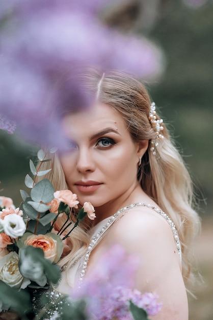 ライラックの茂みの近くのウェディングブーケを持つ若い美しい花嫁 Premium写真