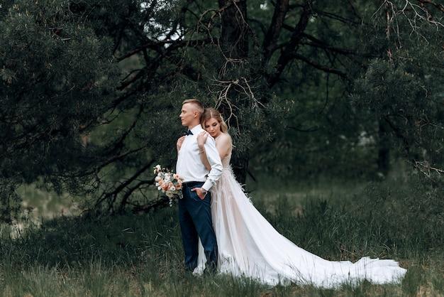 幸せなカップル。若い美しい新郎新婦のウェディングブーケ Premium写真