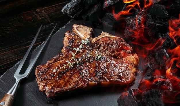 Стейк для барбекю на черной грифельной доске с мясной вилкой и углями гриля Premium Фотографии