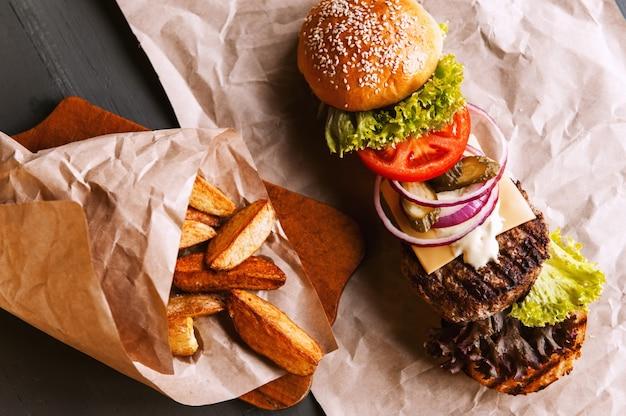 Бургер разложен на составные части на крафт-бумаге на деревянном столе. пакет чипсов. Premium Фотографии