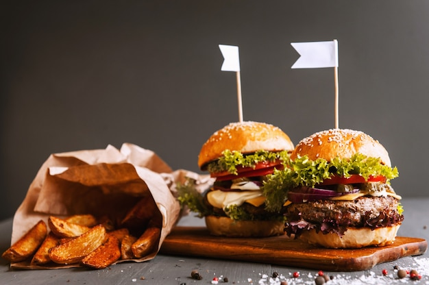 Два аппетитных, вкусные домашние бургеры рубить говядину. на деревянном столе .. маленькие белые флаги вставлены в гамбургеры. Premium Фотографии