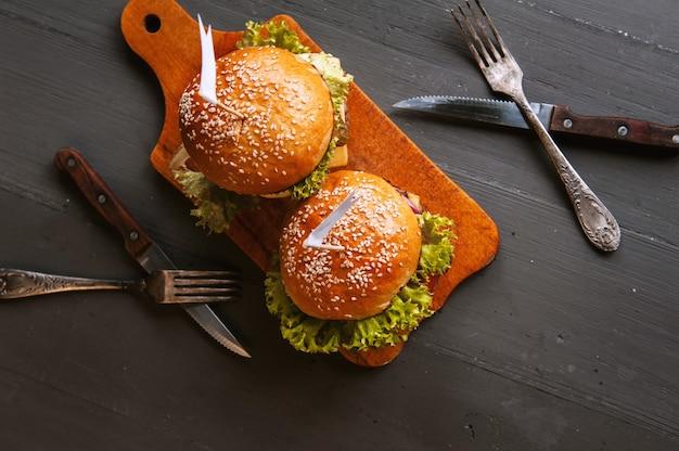Два аппетитных, вкусные домашние бургеры рубить говядину. на деревянном столе. Premium Фотографии