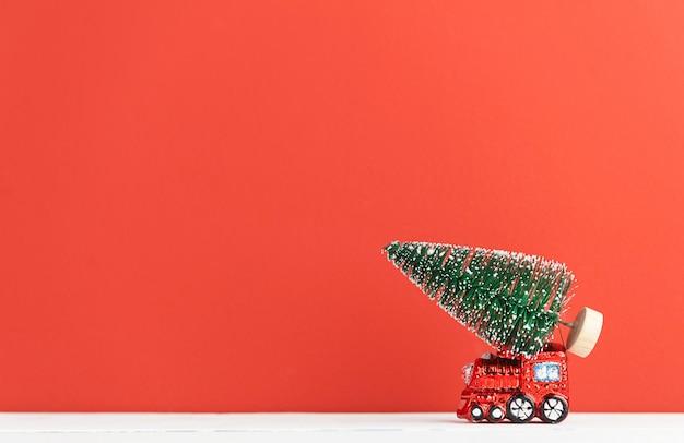 おもちゃの蒸気機関車はクリスマスツリーを運ぶ Premium写真