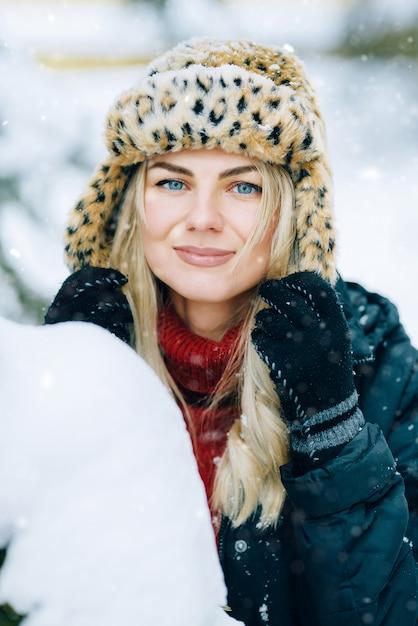 Девушка в модной зимней шапке с леопардовым принтом радуется на снегу Premium Фотографии