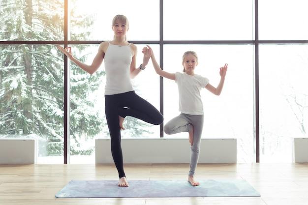 Дочь матери и ребенка в спортзале делает позу йоги Premium Фотографии