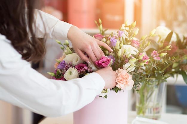 フラワーショップで花の組成を作る女性花屋 Premium写真