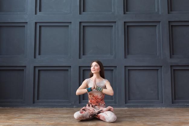 ロータスポーズで座っている間、ヨガの練習の魅力的な女性 Premium写真
