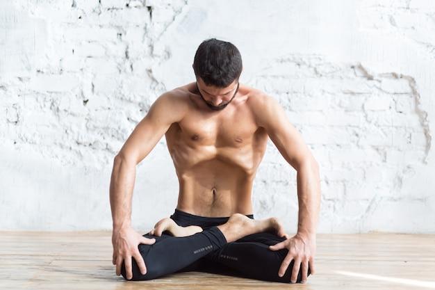 Портрет йога мужчин, делающих упражнения для пресса, он дышит и практикует верхнюю брюшную локоть Premium Фотографии