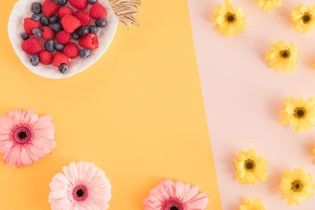 Взгляд сверху таблицы стола лета офиса с цветками и ягодами в плите ананаса на пастельной желтой и розовой предпосылке. рабочий перерыв, летняя концепция. плоская планировка Premium Фотографии