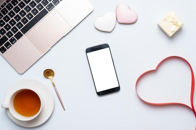 赤いハート、ラップトップ、携帯電話を持つ女性のデスクトップ職場。バレンタインデー構成コンセプト Premium写真