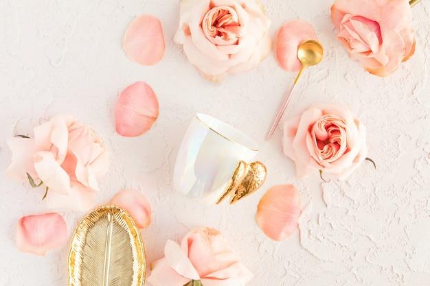 ピンクの花、パステルゴールデンプレート、バラと花びらとスプーンでパステルにスタイリッシュなコーヒーまたは紅茶セット Premium写真