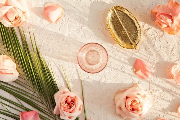 ピンクの牡丹のバラの花、熱帯のヤシの葉、ゴールデンプレート、パステルテクスチャのガラスとスタイリッシュな組成の平面図 Premium写真