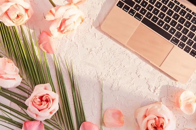熱帯のヤシの葉、ピンクのバラの花、影と太陽の光とパステルでスタイリッシュな組成物のフラットレイアウト Premium写真