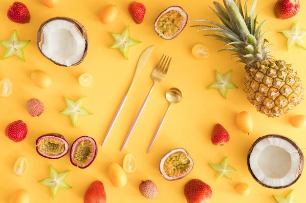 Ананасы, кокосы, ягоды на пастельно-желтых Premium Фотографии