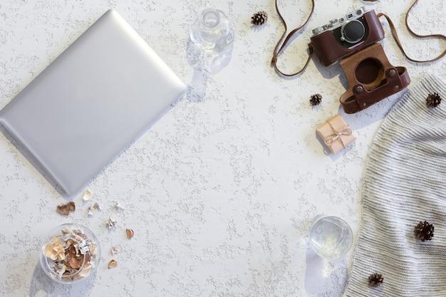 Вид сверху рабочего пространства или офисного стола с ноутбуком, старинный фотоаппарат, одеяло, чашка кофе, имбирное печенье, конус на текстурированном белом фоне Premium Фотографии